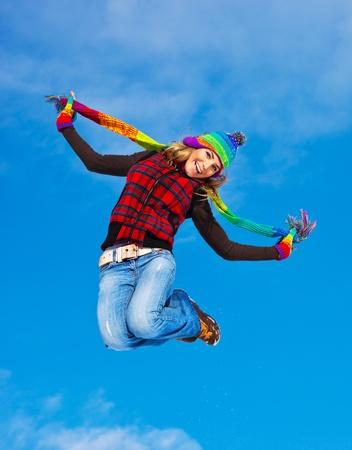 cute teen girl: Счастливая девушка прыжки на фоне голубого неба, подростка на свежем воздухе зимой, женщины веселятся на Рождество, женщина носить разноцветную одежду, свобода и успех концепции Фото со стока