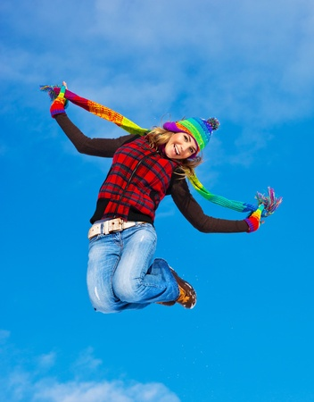 girl woman: Happy girl jumping over blue sky background, teen outdoor winter activities, female having fun at Christmastime, woman wearing colorful clothes, freedom and success concept
