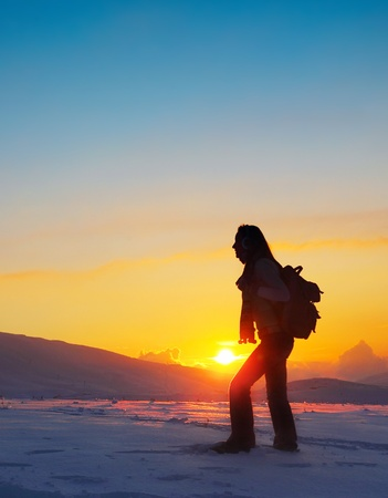 Woman traveler hiking in winter mountains, trekking in wintertime cold snowy weather, girl silhouette over natural colorful sky with bright sunset and beautiful landscape, freedom concept photo