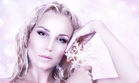 Beautiful woman in Christmas winter style, holding shining snowflake star, glamor female face with bright makeup, sexy girl portrait over abstract pink glowing bokeh holiday background photo
