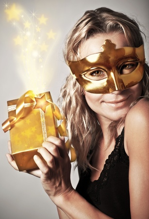 Stylish woman wearing golden mask and holding gift box, celebrating holidays, female receive gold Christmas present, new year eve party photo