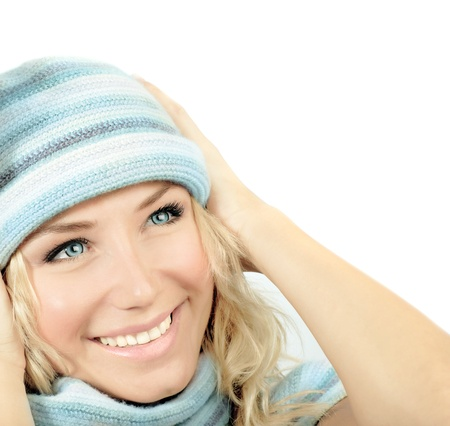Cute girl wearing blue winter hat, beautiful young woman close up on smiling female face, happy teen dressed up in  warm clothing looking up, isolated photo