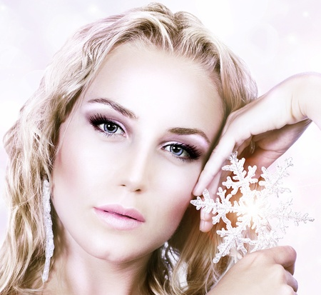 ice queen: Beautiful woman in Christmas winter style, holding shining snowflake star, glamor female face with bright makeup, sexy girl portrait over abstract pink glowing bokeh holiday background Stock Photo