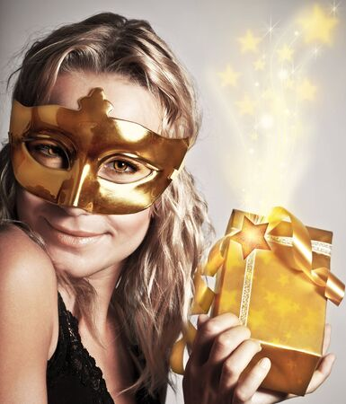 sexy birthday: Stylish woman wearing golden mask and holding gift box, celebrating holidays, female receive gold Christmas present, new year eve party Stock Photo