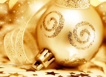 Golden Christmas tree ornament, winter holidays decoration, ornamental decorative bauble, gold background with magic glowing sparks Stock Photo - 11600194