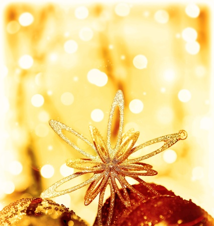 Christmas tree ornament and decoration as border, shining star with baubles, festive background card over abstract bokeh magic golden lights, winter holidays, with copy space photo