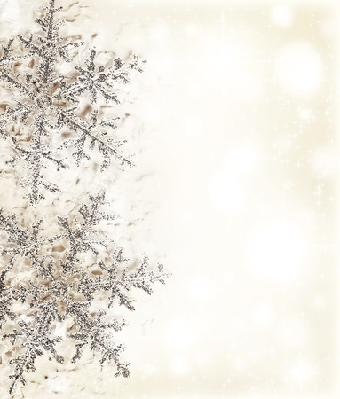 icy: Christmas holiday background with big beautiful snowflake, Christmas tree ornament and decoration, beige card made of abstract blur bokeh magic lights, winter pattern, decorative border design