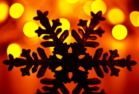 Snowflake background, golden Christmas tree ornament and holiday decoration over abstract blur bokeh lights, silhouette of a snow flake photo