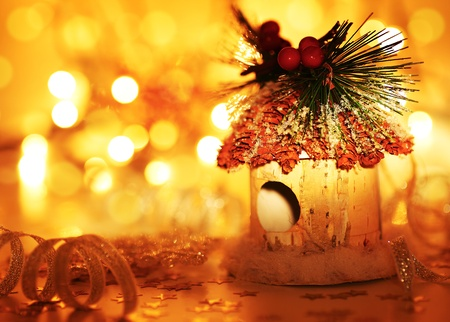 Christmas tree ornament and winter holidays decoration over blur bokeh lights, warm yellow glowing background photo
