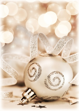 Christmas tree ornament, bauble decoration over bokeh abstract background lights, beautiful silver beige toy with ribbon, home decor for winter holidays, new year eve photo