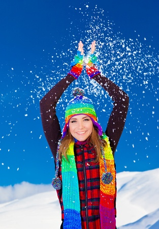 Happy cute girl playing with snow outdoor, throwing it up with hands up, beautiful woman smiling with raised arms to blue sky and nature, young teen female wearing colorful hat, Christmas winter holidays travel and vacation photo