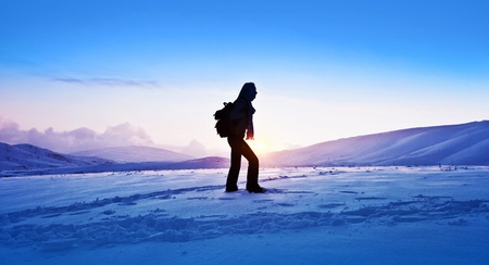 Woman traveler hiking in winter mountains, trekking in wintertime cold snowy weather, girl silhouette over natural blue sky with bright sunset and beautiful landscape, freedom concept photo