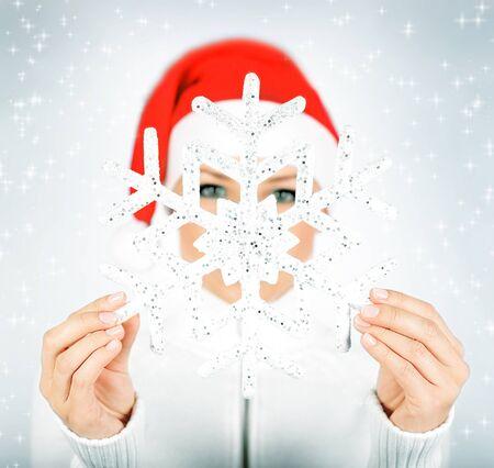 Snowflake in Santa girl hands, holding big flake, selective focus, winter holidays fun, celebrating Christmas photo