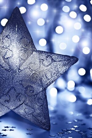 Star decoration, Christmas tree ornament, beautiful blue silver bauble over abstract blur bokeh lights background, decorating home at winter holidays, new year eve photo