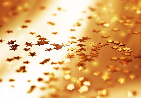 Golden stars background, beautiful shiny abstract starry backdrop, decorative ornamental pattern, Christmas eve winter holiday design, shallow depth of field photo