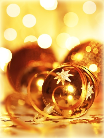 Golden baubles Christmas tree ornament, winter holidays decoration, ornamental decorative toys over gold background with magic glowing blur bokeh lights Stock Photo - 11790597