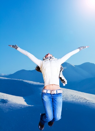 Happy girl jumping over blue sky and snow mountains background, teen outdoor winter activities, female having fun at Christmastime, woman wearing warm clothes, freedom and success concept photo