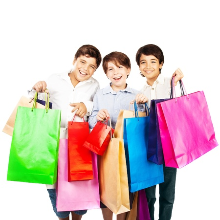 Happy boys with gifts, kids carrying colorful shopping bags with Christmas presents isolated over white background, holidays photo