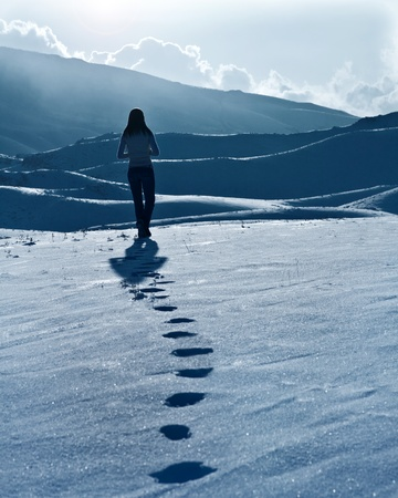 woman walking: Lonely woman silhouette at winter mountains, footprints on the snow, enjoying wintertime nature view,one girl walking outdoor Stock Photo