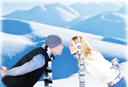Happy couple kissing, side view face portrait, outdoor at winter snowy mountains, people over natural blue wintertime landscape background, Christmas vacation holidays, love concept photo