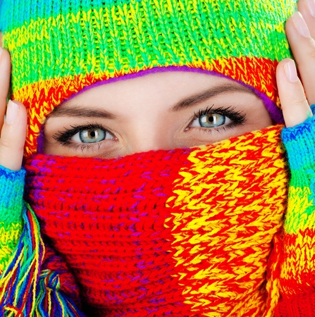 Close up portrait of a womans covered face with beautiful blue eyes, female wearing colorful winter hat, girl having fun outdoor, macro photo