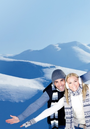 Happy couple having fun, raised arms flying hands, outdoors at winter snowy mountains, people at nature, blue wintertime landscape background, Christmas vacation holidays, love concept photo