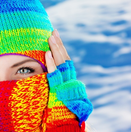 Close up portrait of a womans covered face with beautiful blue eyes, female wearing colorful winter hat, girl having fun outdoor, macro Stock Photo