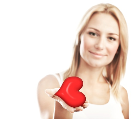 Beautiful woman holding heart in hand, sensual female portrait isolated on white background, cute girl, conceptual image of health care and love, selective focus, shallow dof photo