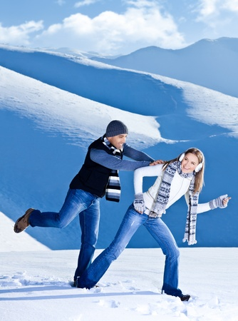Happy couple having fun, running jumping catching fight game, playing outdoors at winter snowy mountains, people at nature, Christmas vacation holidays, love concept photo