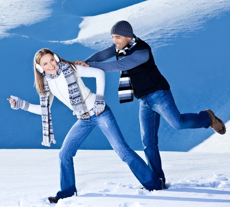 Happy couple having fun, running jumping catching fight game, playing outdoors at winter snowy mountains, people at nature, Christmas vacation holidays, love concept Stock Photo - 12588456