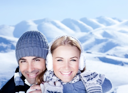Happy couple hugs, holding hands, close up face portrait, outdoor at winter snowy mountains, people over natural blue wintertime landscape background, Christmas vacation holidays, love concept photo