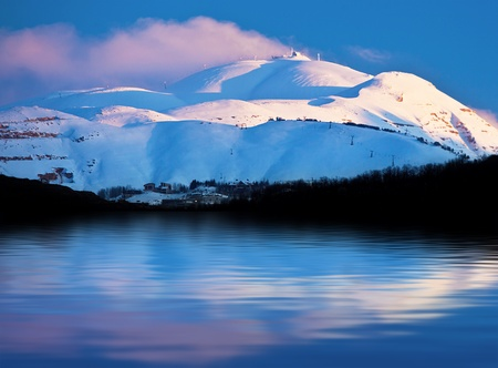 Winter landscape of high mountains covered with snow reflected in fresh lake water, pink sunset over clear blue sky, beautiful seasonal nature,  panoramic wintertime image, cold weather Stock Photo - 12589168