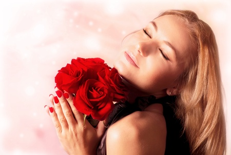 Beautiful female holding red roses bouquet, valentine romantic rose gift, woman over pink abstract background with closed eyes, happy young girl with flowers dreaming photo