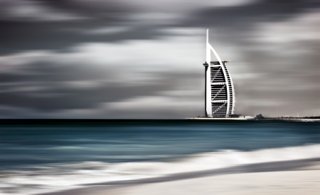 Dark storm, windy landscape of Dubai beach, beautiful nature, seascape with blur motion, Hotel on the sea shore, ocean in United Arab Emirates