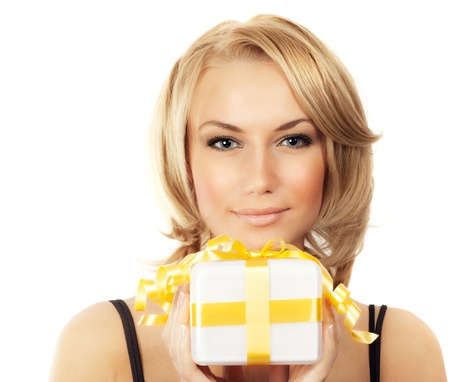 Beautiful female holding gift, blond woman with present, pretty young girl holding golden box, portrait isolated on white background, celebrating holidays photo