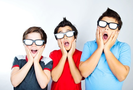 Preteen boys having fun, wearing 3D movie glasses and watching cinema, crazy facial expression, surprised kids, portrait of a screaming teens, children with open mouths photo