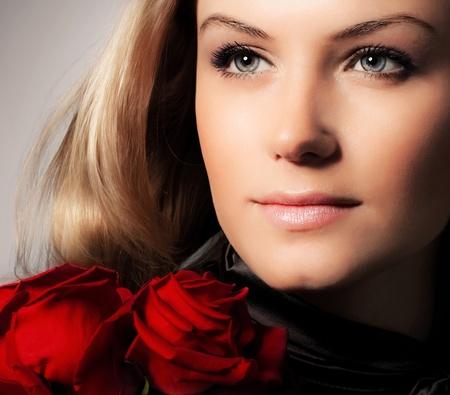 schöne augen: Stilvolle schöne junge Frau mit roten Rosen Bouquet, Nahaufnahme auf wunderschönen Gesicht, zarte Blumen, blond weiblich auf einem dunklen Hintergrund, Kaukasier Modell Mädchen mit frischen Pflanze, Dame verliebt Konzept