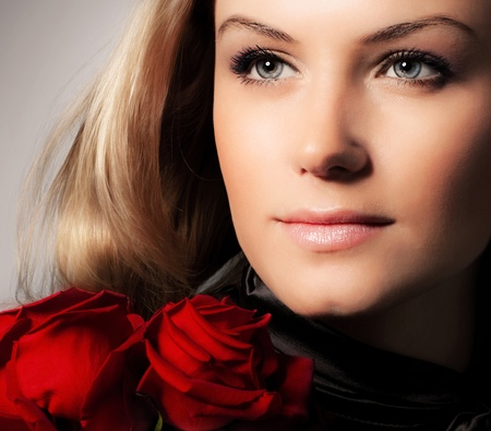 Stylish beautiful young woman holding red roses bouquet, closeup on gorgeous face, tender flowers, blond female over dark background, Caucasian model girl with fresh plant, lady in love concept Stock Photo - 12588531