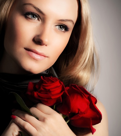 holding mother's hand: Stylish beautiful young woman holding red roses bouquet, tender flowers in hands, blond female over dark background, gorgeous girl with fresh plant, lady in love concept