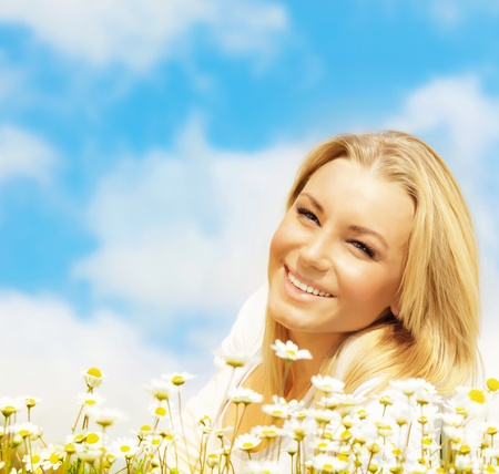 Beautiful woman enjoying daisy field and blue sky, nice female lying down in the meadow of flowers, pretty girl relaxing outdoor, happy young lady and green spring nature in harmony Stock Photo
