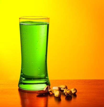 Glass of cold green Irish beer drink isolated on yellow warm background, festival of beer, traditional alcohol for st.Patricks day holiday celebration, lucky clover beverage, studio food still life photo