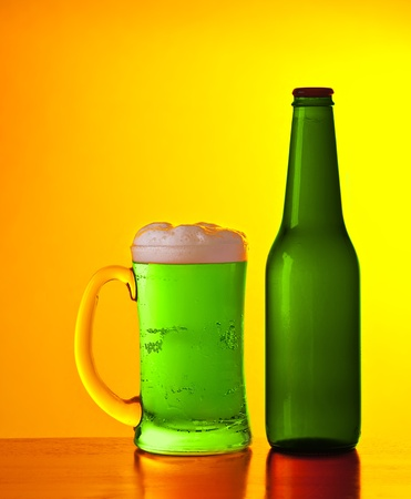 Glass of cold green Irish beer drink isolated on yellow warm background, festival of beer, traditional alcohol for st.Patricks day holiday celebration, lucky clover beverage, studio still life photo