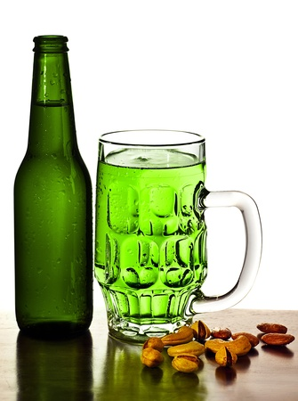 Irish green beer, traditional alcohol for st.Patricks day holiday celebration, lucky clover beverage, glass with nuts, food and drink still life, isolated on white background photo