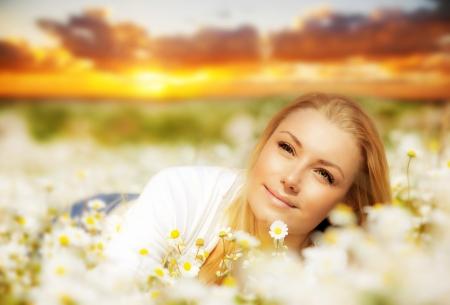 disfrutar: Hermosa mujer disfrutando de campo de margaritas en la puesta de sol, mujer bonita tumbado en el prado de flores, chica linda dama relajarse al aire libre, joven y feliz primavera y la naturaleza en armon�a