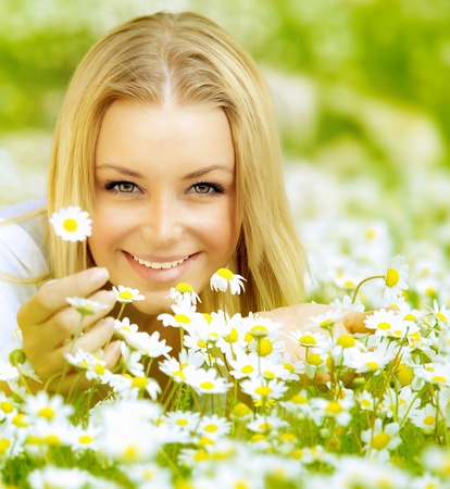 chamomile flower: Beautiful woman enjoying daisy field, nice female lying down in the meadow of flowers, pretty girl relaxing outdoor, having fun, hand holds plant, happy young lady and spring green nature, harmony concept