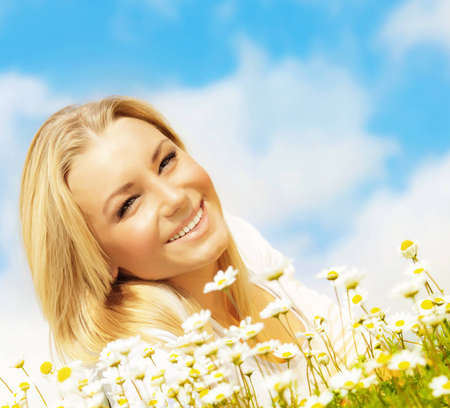 Beautiful woman enjoying daisy field and blue sky, nice female lying down in the meadow of flowers, pretty girl relaxing outdoor, happy young lady and green spring nature in harmony Stock Photo - 12589035