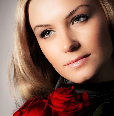 Stylish beautiful young woman holding red roses bouquet, tender flowers in hands, blond female over dark background, gorgeous girl with fresh plant, lady in love concept photo