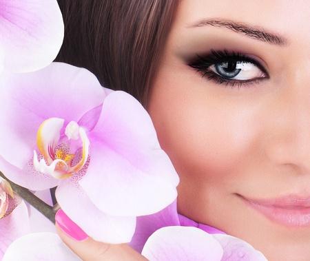 Metà volto della bellissima giovane modella, bella donna con l'occhio fresco fiore rosa orchidea, una parte della testa femminile, ragazza sexy con look elegante, centro benessere e bellezza bianco
