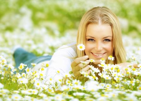 mooie vrouwen: Mooie vrouw genieten van daisy veld, mooie vrouwelijke liggen in de weide van bloemen, mooie meisje ontspannen buiten, plezier maken, met de hand houdt plant, vrolijke jonge dame en de lente groene natuur, harmonie begrip
