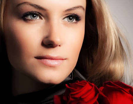 Stylish beautiful young woman holding red roses bouquet, closeup on gorgeous face, tender flowers, blond female over dark background, Caucasian model girl with fresh plant, lady in love concept photo